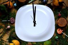 Βέλη ρολογιών σε ένα άσπρο πιάτο που περιβάλλεται από τις ιδιότητες Χριστουγέννων στοκ εικόνα