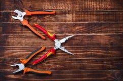 Βέλος που σχεδιάζεται των εργαλείων δύναμης σε ένα ξύλινο υπόβαθρο, ένα σύνολο λεπτός-μυρισμένων δοντιών, πενσών και κόπτη καλωδί Στοκ φωτογραφία με δικαίωμα ελεύθερης χρήσης