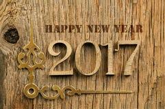Βέλη των ωρών και της νέας επιγραφής έτους στο ξύλινο backgroun στοκ εικόνες
