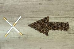 Βέλος από τα φασόλια καφέ με ένα πούρο τέσσερα στο ξύλινο backgrou Στοκ φωτογραφία με δικαίωμα ελεύθερης χρήσης