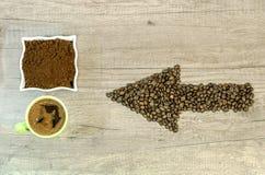 Βέλος από τα φασόλια καφέ με ένα φλυτζάνι του φρέσκου επίγειου καφέ και το πλήρες πράσινο φλυτζάνι Στοκ εικόνες με δικαίωμα ελεύθερης χρήσης