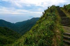 Βήματα κατά μήκος μιας απότομης κορυφογραμμής στο ιστορικό ίχνος Caoling στην Ταϊβάν, με το νησί χελωνών στο υπόβαθρο Στοκ φωτογραφία με δικαίωμα ελεύθερης χρήσης