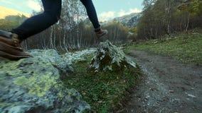 Βήματα ποδιών του οδοιπόρου που υπαίθρια περπάτημα των ποδιών στη δύσκολη έκταση άλμα πέρα από τις πέτρες απόθεμα βίντεο