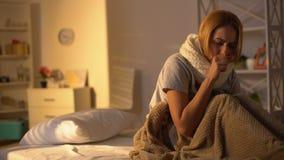 Βήχοντας άρρωστη κυρία που φορά το μαντίλι που βρίσκεται στο κρεβάτι, επώδυνος λαιμός, σύμπτωμα βρογχίτιδας απόθεμα βίντεο