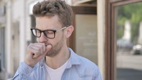 Βήχοντας άρρωστος νεαρός άνδρας που στέκεται υπαίθριος απόθεμα βίντεο