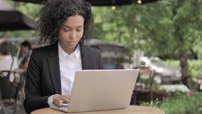 Βήχοντας αφρικανική γυναίκα που εργάζεται στο lap-top στον υπαίθριο καφέ φιλμ μικρού μήκους