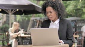 Βήχοντας αφρικανική επιχειρηματίας που εργάζεται στο lap-top στον υπαίθριο καφέ φιλμ μικρού μήκους