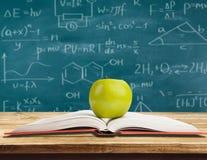 Βίβλος και πράσινο μήλο που απομονώνονται στο υπόβαθρο Στοκ Εικόνα