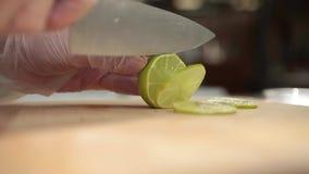 Βίντεο από την κουζίνα του εστιατορίου Ο μάγειρας κόβει τον πράσινο ασβέστη με ένα μεγάλο μαχαίρι