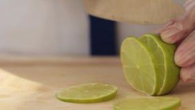 Βίντεο από την κουζίνα του εστιατορίου Ο μάγειρας κόβει τον πράσινο ασβέστη με ένα μεγάλο μαχαίρι Κινούμενη φωτογραφική μηχανή