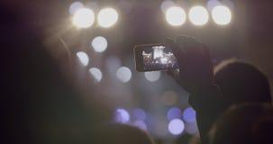 Βίντεο καταγραφής ατόμων θεατών της σκηνής μπροστά από τα φωτεινά επίκεντρα μέσω του smartphone στην υπαίθρια συναυλία μουσικής φιλμ μικρού μήκους