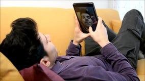 Βίντεο νεαρών άνδρων που κουβεντιάζει με το PC ταμπλετών που χαμογελά για τη κάμερα απόθεμα βίντεο