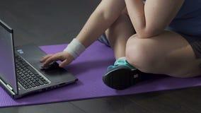 Βίντεο προσοχής εφήβων στο lap-top στο πάτωμα, που τρυπά τα άκρα δακτύλου ενάντια στο χαλί γιόγκας απόθεμα βίντεο