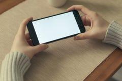 Βίντεο προσοχής κοριτσιών ή παιχνίδι παιχνιδιού στο κινητό τηλέφωνο στην οριζόντια θέση οθόνη για app το πρότυπο, παρουσίαση Στοκ εικόνα με δικαίωμα ελεύθερης χρήσης