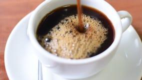 Βίντεο της τοποθέτησης του μαύρου καφέ σε ένα άσπρο φλυτζάνι απόθεμα βίντεο