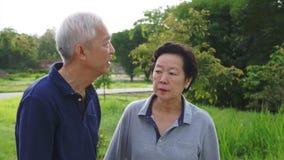 Βίντεο του ευτυχούς ασιατικού ανώτερου ζεύγους που δείχνει, που μιλά και περίπατος μέσω του πάρκου με το υπόβαθρο φύσης φιλμ μικρού μήκους