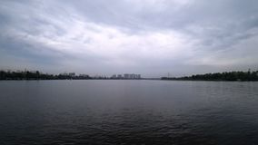 Βίντεο χρόνος-σφάλματος στον ποταμό από ένα σκάφος που πανιά στην ακτή της πόλης Θλιβερός καιρός το βράδυ Νερό απόθεμα βίντεο