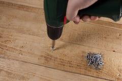 Βίδα που βιδώνεται με το τρυπάνι στον ξύλινο πίνακα Στοκ Εικόνες