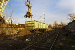 Βαγόνι εμπορευμάτων κάτω από έναν υδραυλικό γερανό Βαγόνι εμπορευμάτων κάτω από το γερανό Τραίνο και γερανός στοκ εικόνες