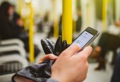 Βαγόνι εμπορευμάτων σωλήνων τραίνων μετρό γυναικών insde που χρησιμοποιεί το smartphone για να δει το μ Στοκ φωτογραφίες με δικαίωμα ελεύθερης χρήσης