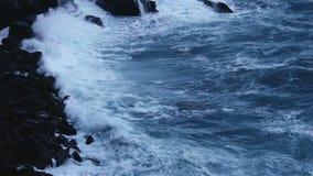 Βαθιά μπλε κύματα θάλασσας που καταβρέχουν και που συντρίβουν στις πέτρες απότομων βράχων, θυελλώδης καιρός απόθεμα βίντεο