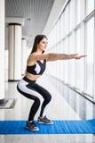 Βαθιά στάση οκλαδόν Πλάγια όψη της νέας όμορφης γυναίκας sportswear που κάνει τη στάση οκλαδόν και που κρατά τους αλτήρες στεμένο στοκ φωτογραφίες με δικαίωμα ελεύθερης χρήσης