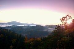 Βαθιά misty κοιλάδα μέσα στη χαραυγή Ομιχλώδες και misty πρωί στο λοφώδες σημείο άποψης Στοκ Εικόνες