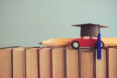 Βαθμολόγηση ΚΑΠ, ξύλινο αυτοκίνητο και μεγάλο μολύβι πέρα από τα βιβλία στο μπλε Στοκ Φωτογραφίες