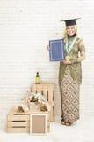 Βαθμολογημένος θηλυκό σπουδαστής της Ινδονησίας που φορά τα παραδοσιακά ενδύματα στοκ εικόνα με δικαίωμα ελεύθερης χρήσης