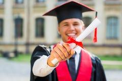 Βαθμολόγηση: Σπουδαστής που στέκεται με το δίπλωμα Στοκ φωτογραφία με δικαίωμα ελεύθερης χρήσης