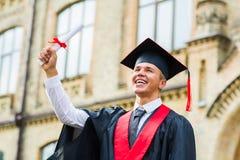 Βαθμολόγηση: Σπουδαστής που στέκεται με το δίπλωμα Στοκ Φωτογραφίες