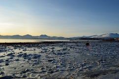 Βαθύς μπλε πάγος στην ακροθαλασσιά με το φιορδ και το χιονώδες βουνό Στοκ Εικόνες