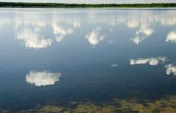 Βαθύς μπλε θερινός ουρανός με τα άσπρα σύννεφα που απεικονίζουν στην καθαρή λίμνη W Στοκ Εικόνες