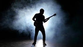 Βαθύ άτομο κιθαριστών σκιαγραφιών στον καπνό κίνηση αργή Μαύρη ανασκόπηση απόθεμα βίντεο