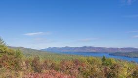 Βαθύ μπλε της λίμνης George που συμπληρώνεται από τα χρώματα πτώσης Στοκ Φωτογραφίες