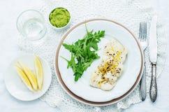 Βακαλάος που ψήνεται με το λεμόνι και τα καρυκεύματα με το arugula και το πολτοποίηση πράσινο pe Στοκ Εικόνα