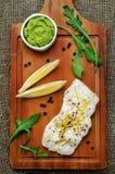 Βακαλάος που ψήνεται με το λεμόνι και τα καρυκεύματα με το arugula και το πολτοποίηση πράσινο pe Στοκ Φωτογραφίες