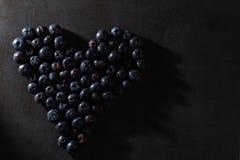 Βακκίνια σε μια μορφή καρδιών Συγκρατημένος φωτισμός στοκ φωτογραφία