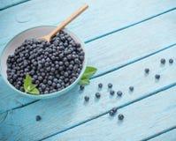 Βακκίνια στο πιάτο στον μπλε ξύλινο πίνακα Στοκ φωτογραφία με δικαίωμα ελεύθερης χρήσης