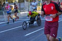 ΒΑΛΈΝΘΙΑ, ΙΣΠΑΝΙΑ - 2 ΔΕΚΕΜΒΡΊΟΥ: Οι δρομείς ανταγωνίζονται σε μια αναπηρική καρέκλα στο XXXVIII μαραθώνιο της Βαλένθια στις 18 Δ στοκ εικόνα με δικαίωμα ελεύθερης χρήσης