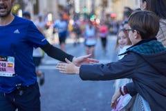 ΒΑΛΈΝΘΙΑ, ΙΣΠΑΝΙΑ - 2 ΔΕΚΕΜΒΡΊΟΥ: Οι δρομείς τινάζουν τα χέρια με τους συμμετέχοντες στο XXXVIII μαραθώνιο της Βαλένθια στις 18 Δ στοκ φωτογραφίες