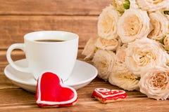 βαλεντίνος ημέρας s γάμος Μια καρδιά φλιτζανιών του καφέ και δύο μελοψωμάτων σε ένα υπόβαθρο των τριαντάφυλλων Στοκ φωτογραφία με δικαίωμα ελεύθερης χρήσης