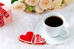 βαλεντίνος ημέρας s γάμος Μια καρδιά φλιτζανιών του καφέ και δύο μελοψωμάτων σε ένα υπόβαθρο των τριαντάφυλλων Στοκ Εικόνα