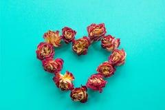 βαλεντίνος καρτών s Σύμβολο καρδιών φιαγμένο από ξηρά τριαντάφυλλα σε ένα μπλε υπόβαθρο Η τοπ άποψη, επίπεδη βάζει Στοκ Εικόνες