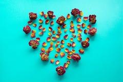 βαλεντίνος καρτών s Σύμβολο καρδιών φιαγμένο από ξηρά τριαντάφυλλα σε ένα μπλε υπόβαθρο Η τοπ άποψη, επίπεδη βάζει διάστημα αντιγ Στοκ Εικόνες