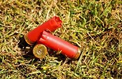 Βαλμένες φωτιά κασέτες σφαιρών πυροβόλων όπλων κοχυλιών κενές κόκκινες καλυμμένες Στοκ Εικόνες