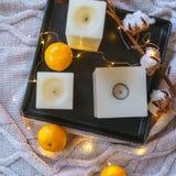 Βαμβάκι χειμερινής ακόμα ζωής και tangerines και κεριά στο μαύρο tra στοκ φωτογραφίες