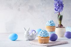 Βανίλια Πάσχας cupcakes, αυγά, χαριτωμένοι λαγουδάκι και υάκινθος σε ένα δοχείο στοκ φωτογραφία