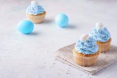 Βανίλια Πάσχας cupcakes με τα μπλε αυγά παγώματος και καραμελών στοκ εικόνα με δικαίωμα ελεύθερης χρήσης