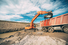 Βαρέων καθηκόντων μηχανήματα, λεπτομέρειες της εθνικής οδού οικοδόμησης εκσκαφέων και φορτώνοντας φορτηγά εκφορτωτών Στοκ Εικόνες